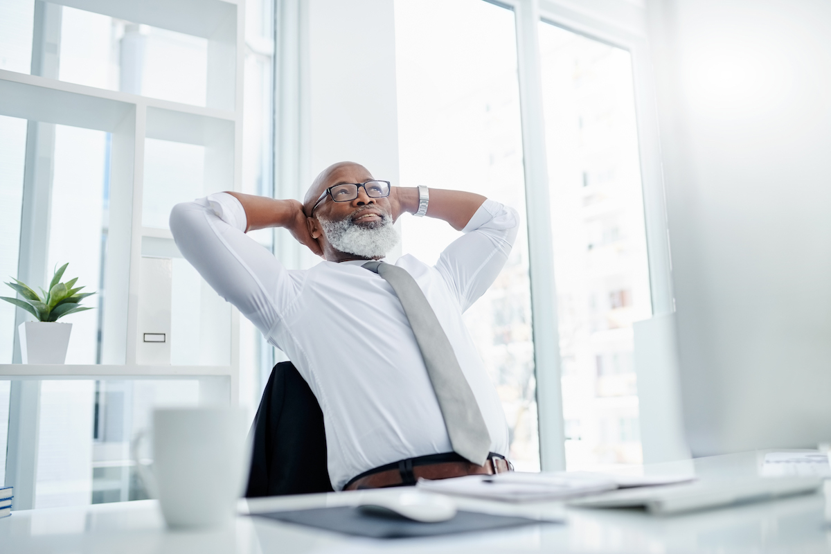 Black middle aged business man leaning back in office chair